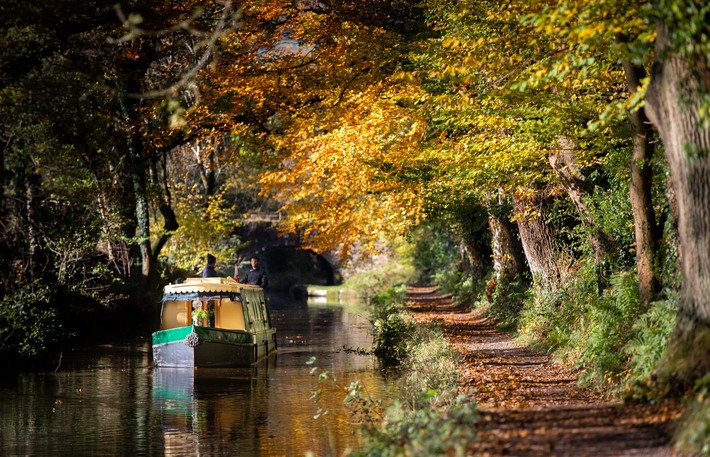 a canal boat surrounded by the solours of autumn